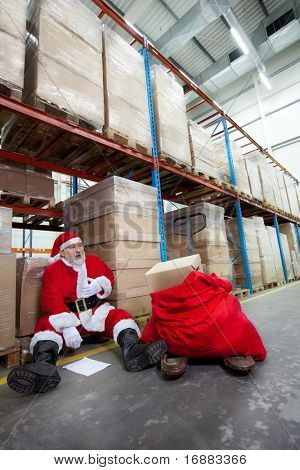 Overworked santa claus with pain in chest with list of gifts to buy  in storehouse