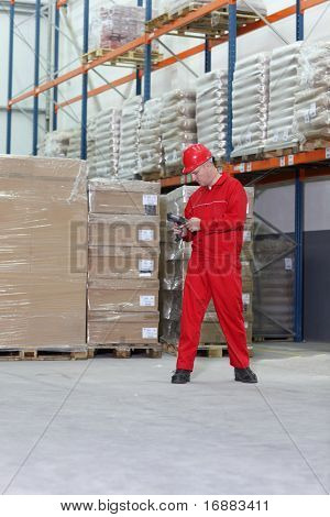 worker in red uniform with bar code reader preparing to work in warehouse