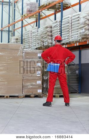 worker in red uniform checking inventory stocks at a factory storeroom