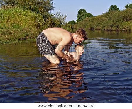 father bathes its child in river