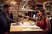 Romantic couple in love have dinner on Valentineâ??s evening in restaurant poster
