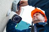 Technician worker installing video surveillance camera on wall poster