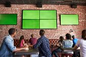 Rear View Of Friends Watching Game In Sports Bar On Screens poster