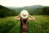 Woman Traveler With Backpack Holding Hat And Looking At Amazing Mountains And Forest, Wanderlust Tra poster