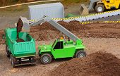 stock photo of dumper  - Green dumper and earthmover on a road building - JPG