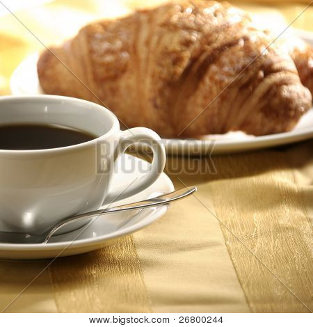 close up image of croissant and tea