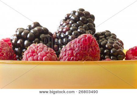 raspberries and blackberries in orange pot