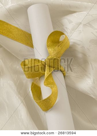diploma with gold ribbon on the white silk