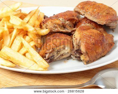 Un plato de servir con muslos de pollo asado limón y patatas fritas o chips, con una porción spoo