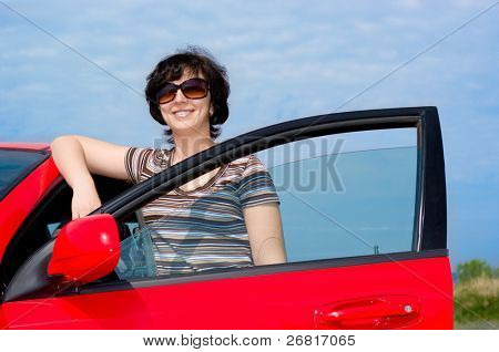 Young smiling woman with red car
