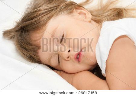 Sleeping little girl on bed