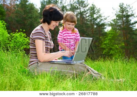Little girl and mother with laptop outdoor