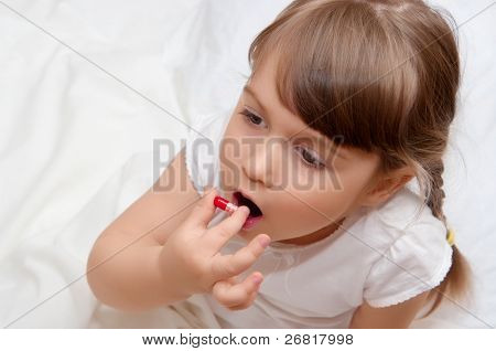 Little girl with red pill