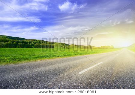 Asphalt rural road to sunrise