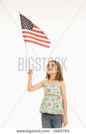 Chica sosteniendo la bandera americana.