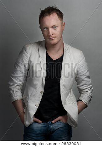 Portrait of a handsome young man with red hair wearing white jacket, black  shirt and jeans
