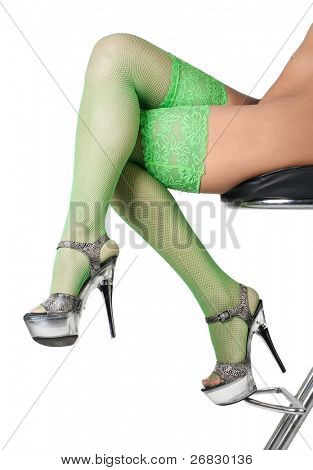 Close-up of female legs in green fishnet stockings against white background