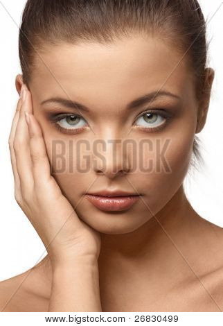 Closeup of a pensive beautiful woman with makeup touching her face and looking at camera