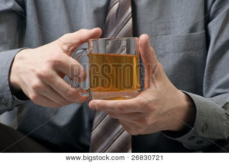 Close-up of a cup of green tea in hands of a businessman