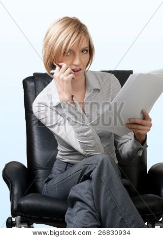 Attractive businesswoman sitting in the armchair and holding documents and pen, isolated on blue