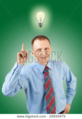 Handsome businessman with finger pointing up and with light bulb over his head, over green background