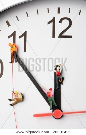 Mountaineers Scaling The Hands Of A Clock