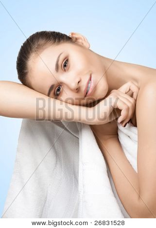 Portrait of pretty young woman wearing white towel against blue background