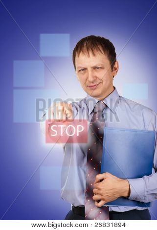 Portrait of a confident businessman pushing on button stop, over blue background