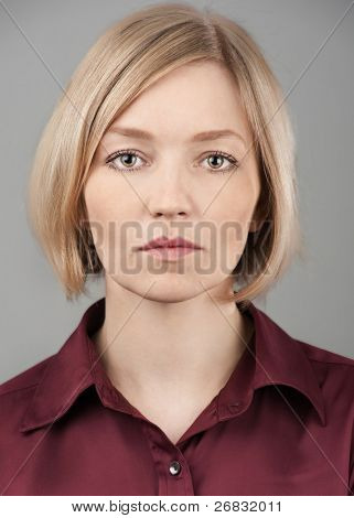 Close up portrait of a pretty young blond woman with serious face