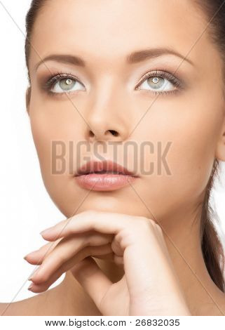 Portrait of beautiful spa girl with brown hair touching her chin, over white background