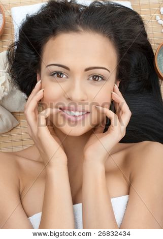 Close-up portrait of young beautiful spa woman laying on bamboo mat at spa salon and smiling