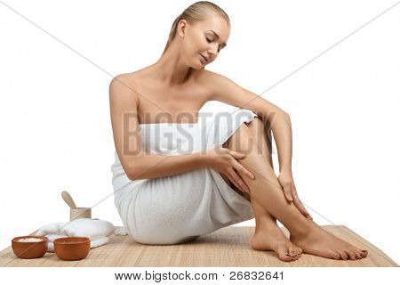Portrait of young beautiful spa woman sitting on bamboo mat at a spa salon. Isolated on white background.