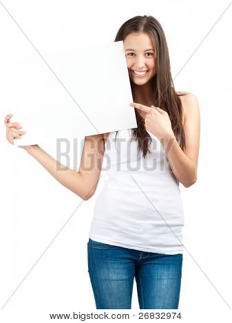 Full length portrait of a happy young casual woman holding a blank signboard and pointing, isolated on white background