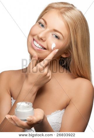 Portrait of young beautiful woman applying moisturizer cream on her face, isolated on white background
