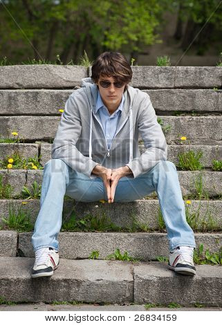 Portrait of handsome young man wearing sunglasses sitting on the stairs in the park