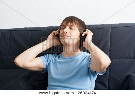 Portrait of a relaxed young man sitting on sofa and listening to music on headphone