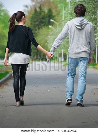 Young couple walking together hand by hand  in park, rear view