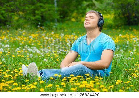Retrato de un hombre joven tranquilo sentado en el césped en el parque y escuchando música en los auriculares
