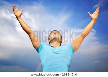 Happy young man with raised arms and closed eyes against blue sky