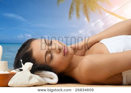 Portrait of young beautiful spa woman lying on bamboo mat and smiling. Against blue sky background.