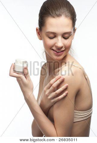 Portrait of young beautiful Woman Anwendung Feuchtigkeitscreme Creme auf der Schulter, isoliert auf weiß