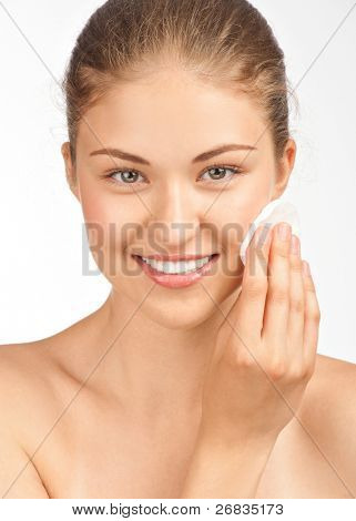 Portrait of young beautiful woman with cotton swab cleaning her face
