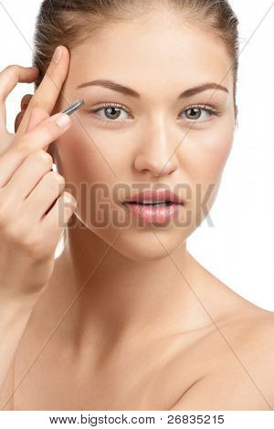 Young beautiful woman plucking her eyebrows with tweezers. Isolated on white background