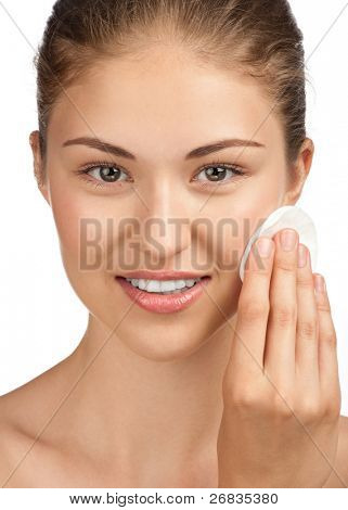 Close-up portrait of young beautiful woman with cotton swab cleaning her face