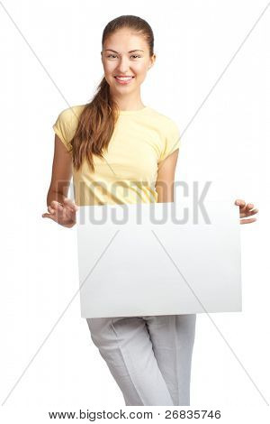 Portrait of a happy young casual woman standing and holding a blank signboard, isolated on white background