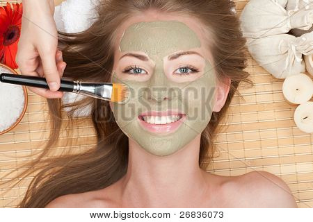 Close-up of young beautiful woman with clay facial mask at spa salon