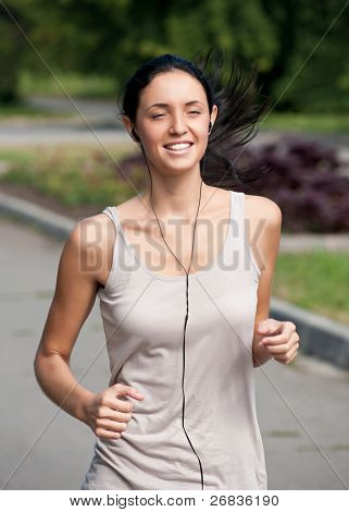 Young beautiful woman running in park and listening to music