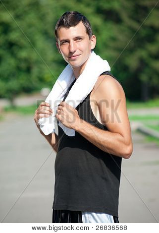 Young muscular man with a white towel have a rest after jogging in park