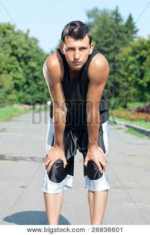 Young muscular man have a rest after jogging in park
