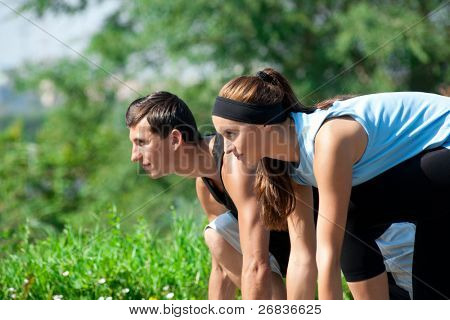 Young fitness couple of man and woman ready to start running